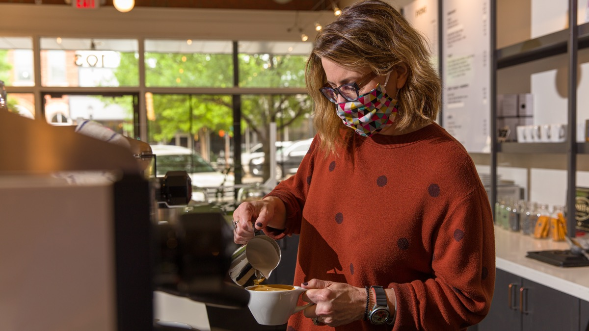 """Lori Dickinson-Black, co-owner of Cafe Evoke in downtown Edmond, makes latte while wearing a mask. Since reopening in May they have adhered to social distancing safety measures. (Photo: <a href=""""https://edmondbusiness.com/author/brent.fuchs/"""">Brent Fuchs</a>)"""