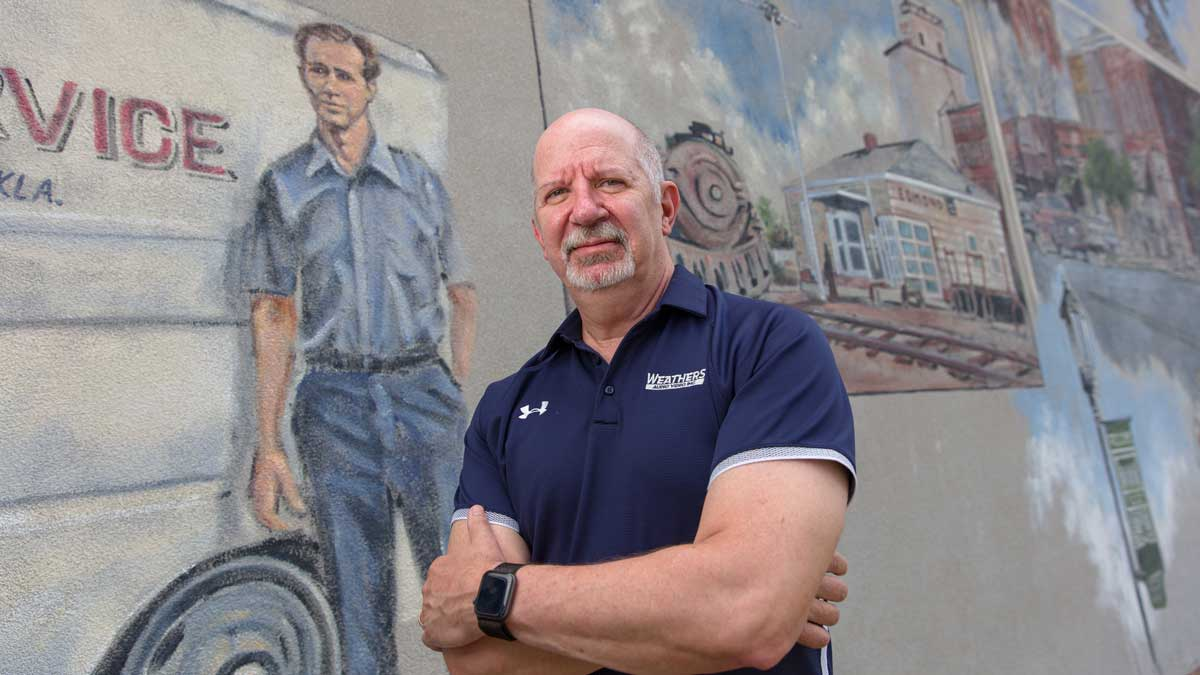 """Scott Weathers in front of the mural of his father, Jack Weathers (Photo: <a href=""""https://edmondbusiness.com/author/brent-fuchs/"""">Brent Fuchs</a>)"""