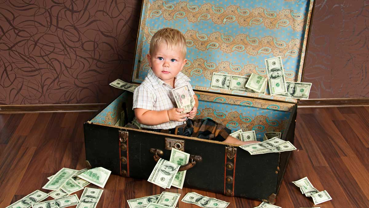 Child in suitcase surrounded by money