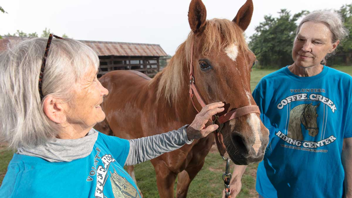 """Coffee Creek Riding Center Director Joy Milligan and Assistant Director Linda Cloud with a therapeutic horse (Photo: <a href=""""https://edmondbusiness.com/author/brent-fuchs/"""">Brent Fuchs</a>)"""