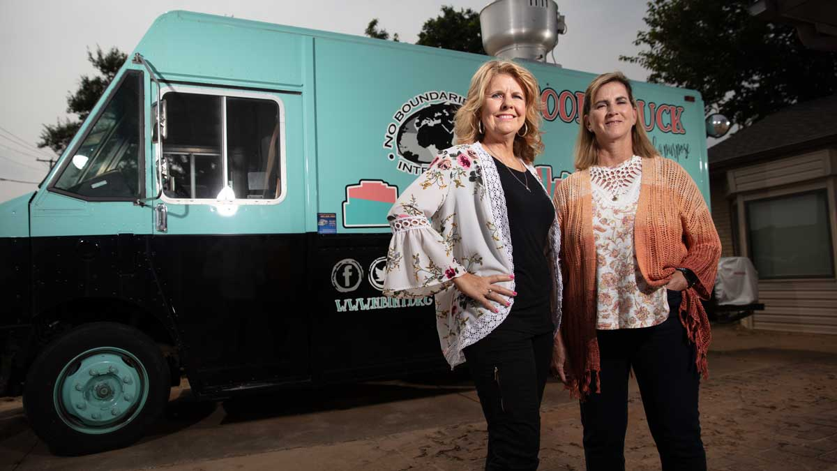 """Lori Basey and Sandy Orchard, founders of No Boundaries International, in front of the food truck they use as one method of outreach (Photo: <a href=""""https://edmondbusiness.com/author/brent-fuchs/"""">Brent Fuchs</a>)"""